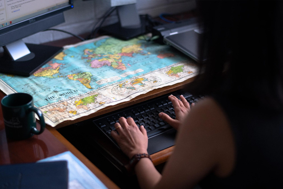Dr. Asha Shenoi uses her computer with a map of the world on her desktop.