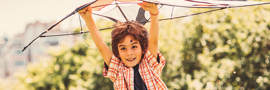 Little boy playing with a kite in the park.