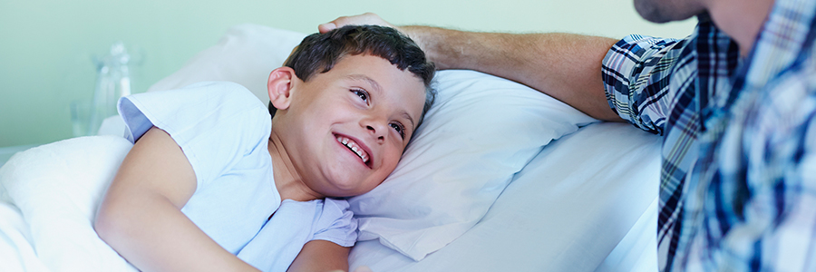 Happy boy holding father's hand while lying in bed at hospital bed