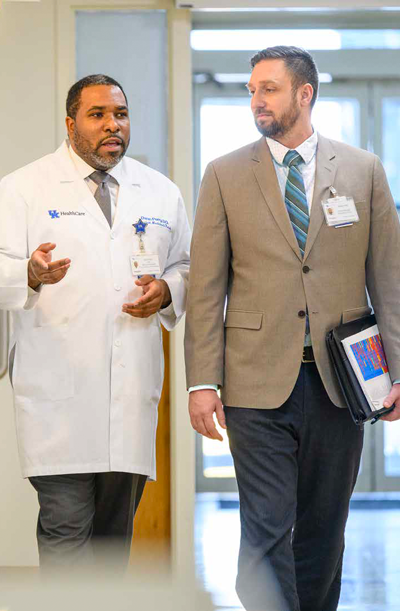 A doctor and administrator talk as they walk through the hospital.