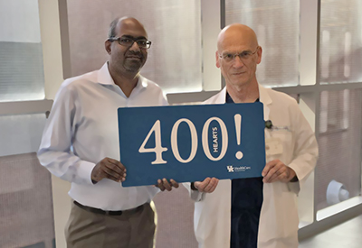 Dr. Sekela and Dr. Raj holding a sign that reads over 400 hearts
