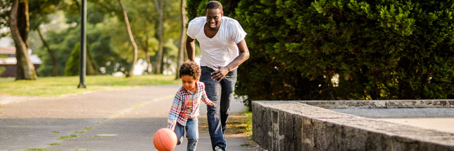 A father and his young son play with a basketball.