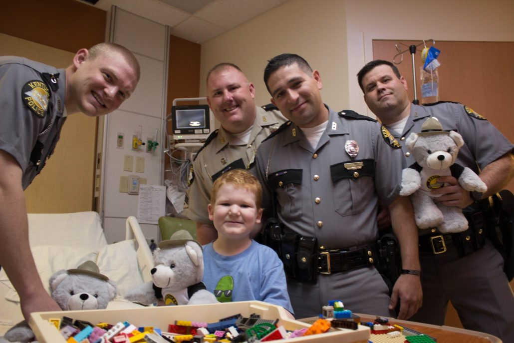 Four Kentucky State Troopers deliver a teddy bear to a young boy at Kentucky Children's Hospital.