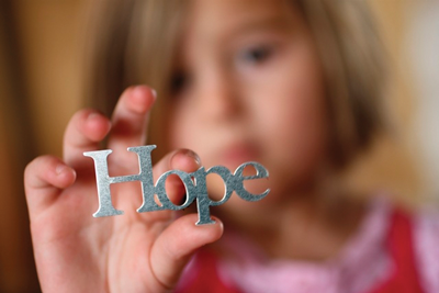 "A girl holds letters spelling ""hope."""
