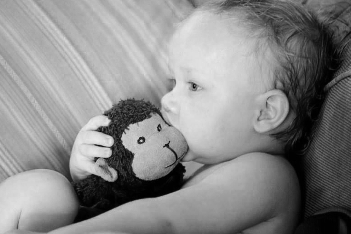 Baby picture of Ezra Yost with his toy, Stinky Monkey.
