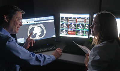 John Gurley, MD discusses a scan with Kate Moore, PA-C.
