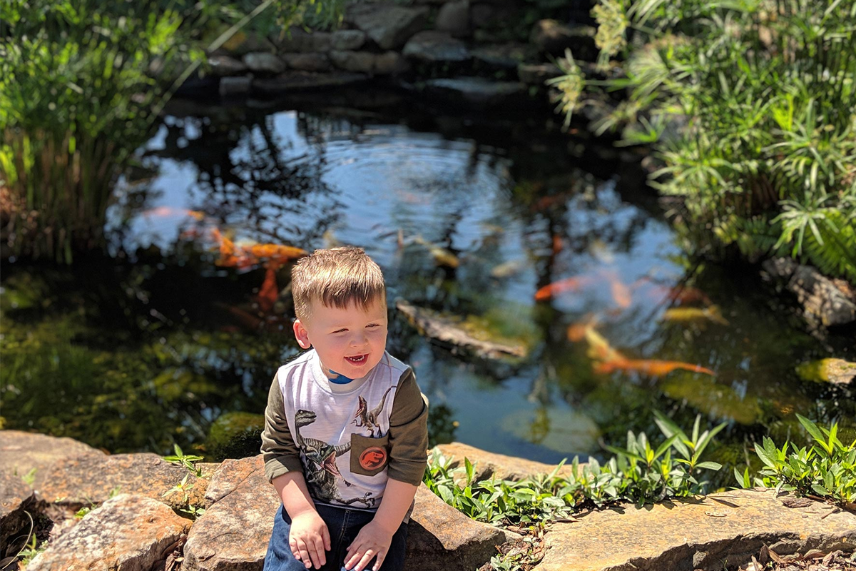 Kase Chaney sits beside a pond full of goldfish.