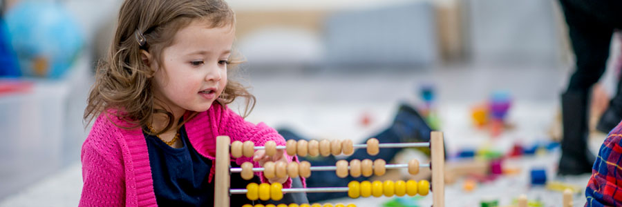 A little girl plays with counting beads (abacus).