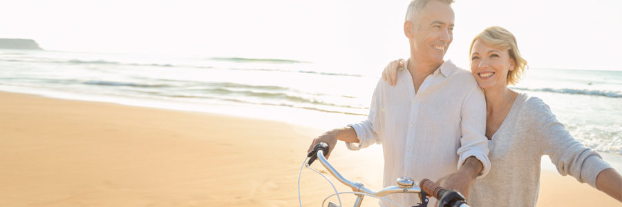 A middle-aged couple on the beach with bicycles.