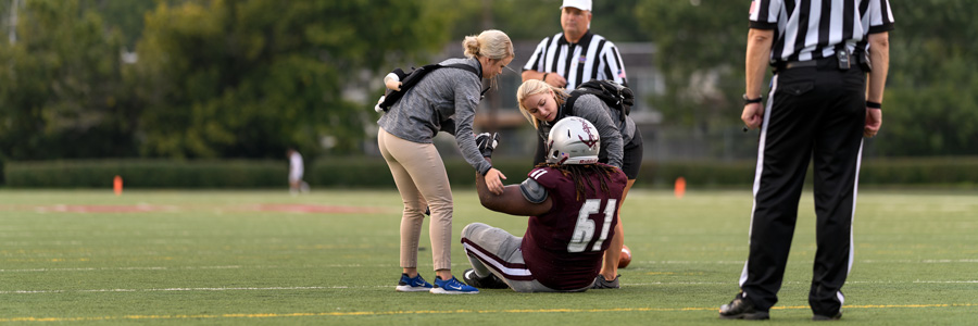 Athletic trainers assist an injured football player.