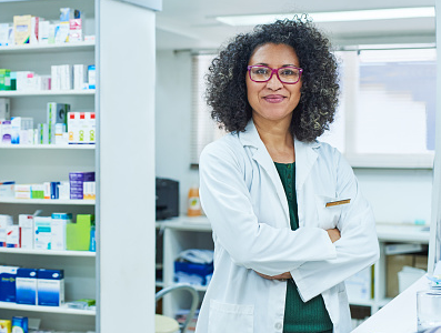 A pharmacist with her arms folded stands in the pharmacy.