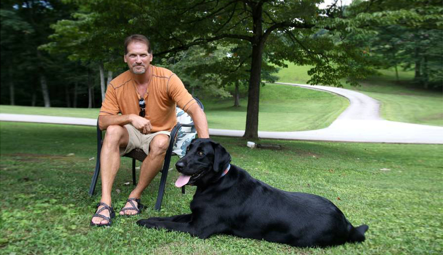 Myrl Sizemore sits outdoors with his dog, Sarge, at his feet.