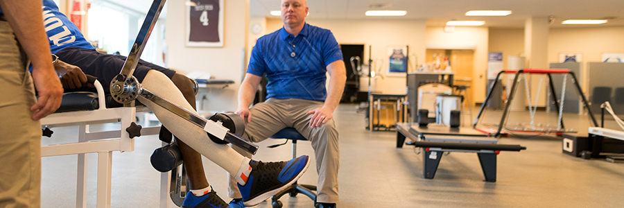 A sports rehabilitation patient lifts weights with his leg as two physical therapists watch.