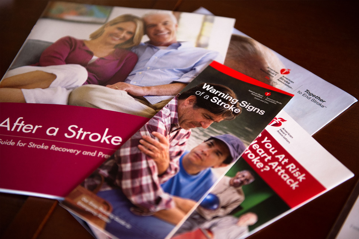 Brochures on stroke and related topics are spread out on a table.