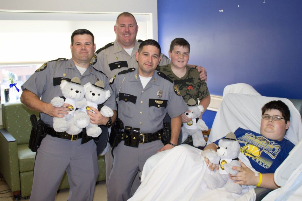 Three Kentucky State Troopers deliver a teddy bear to a boy at KCH with his brother.