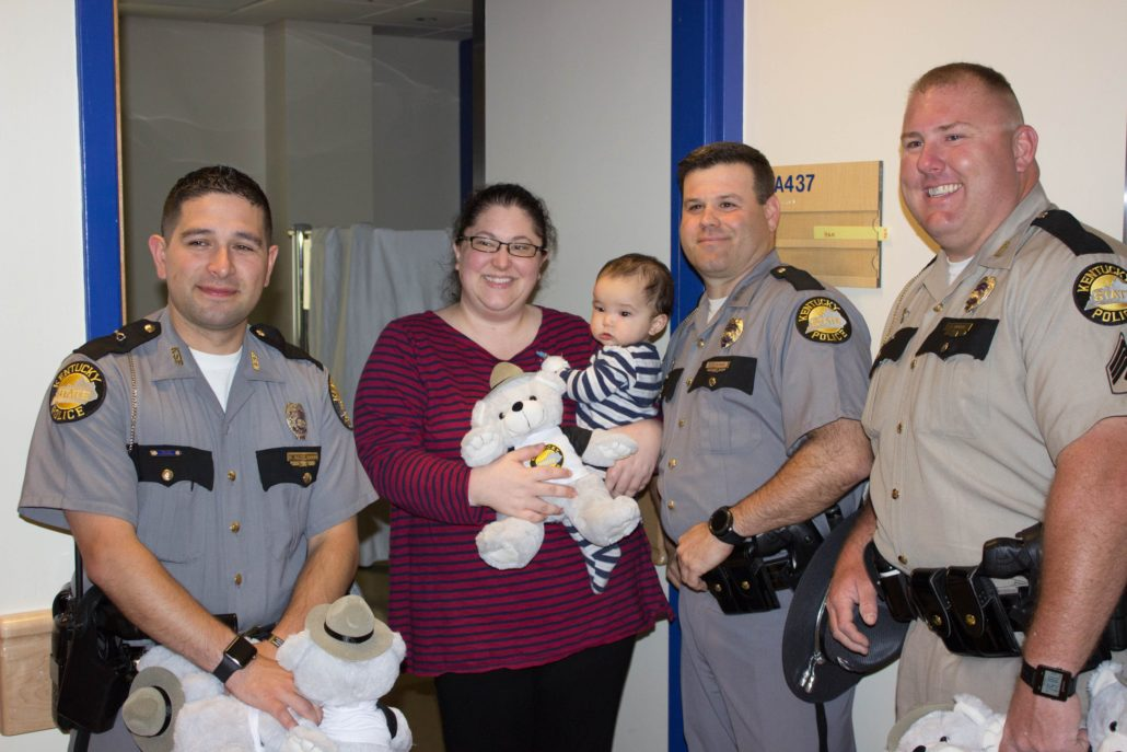 Three Kentucky State Troopers deliver a teddy bear to a young patient and mom.