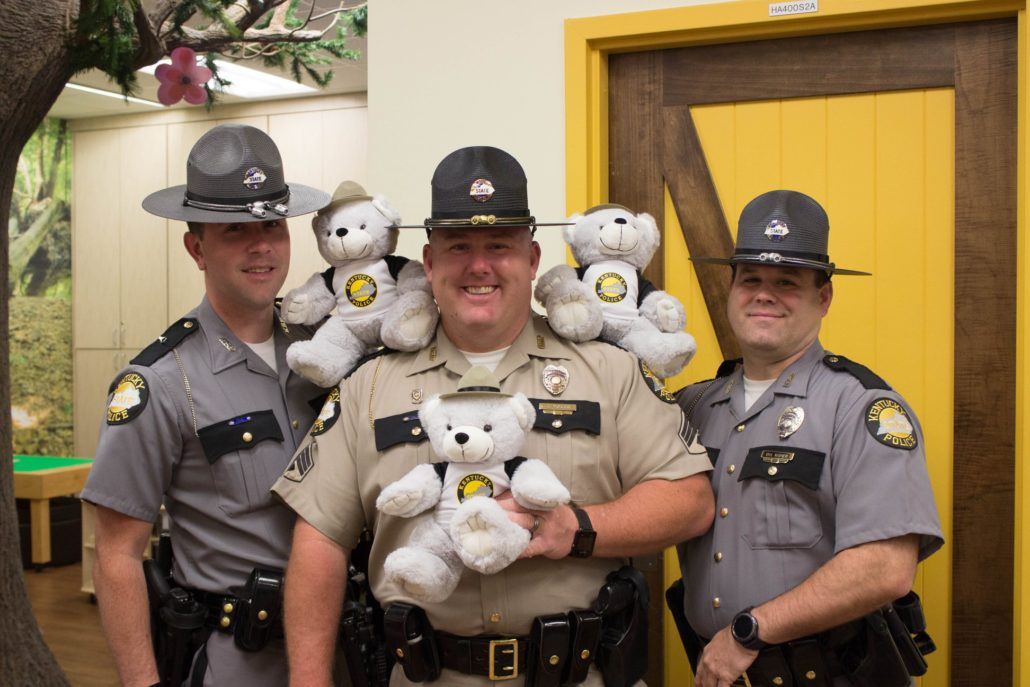 Three Kentucky State Troopers pose with teddy bears.