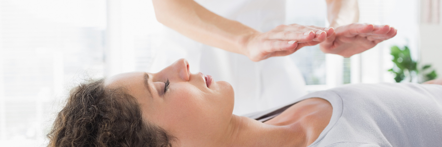 A woman receives Reiki treatment.