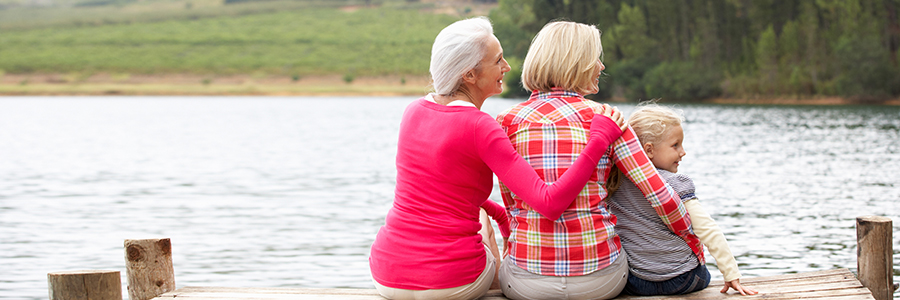 Grandmother, child and grandchild sitting on a dock